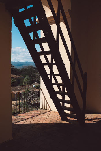 Staircase of building against sky seen through window