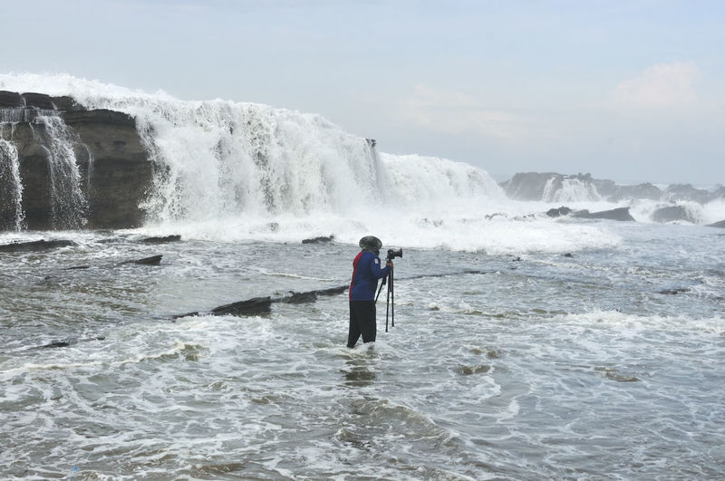 Photographer Standing With Tripod In Sea Against Waterfall Against Sky
