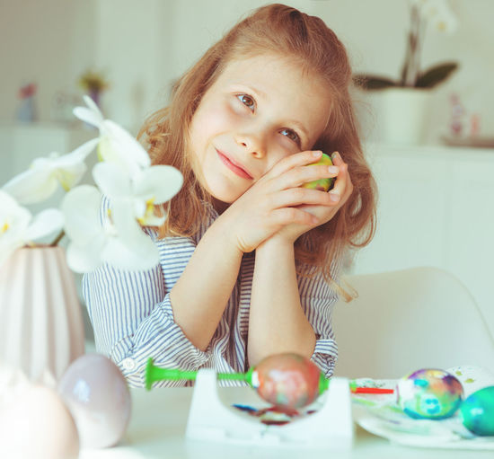 Cute girl holding easter egg while sitting at home