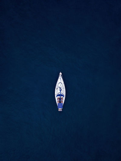 Aerial view of a solo sailing boat at deep blue sea
