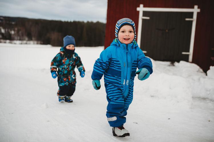 Full length of boys on snow in park during winter