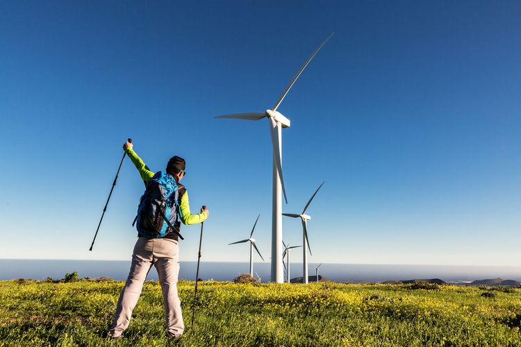 Full length of man standing against wind turbines