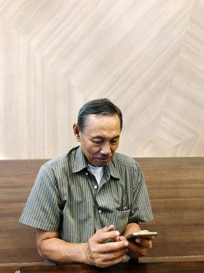 Senior man using mobile phone against wall at home