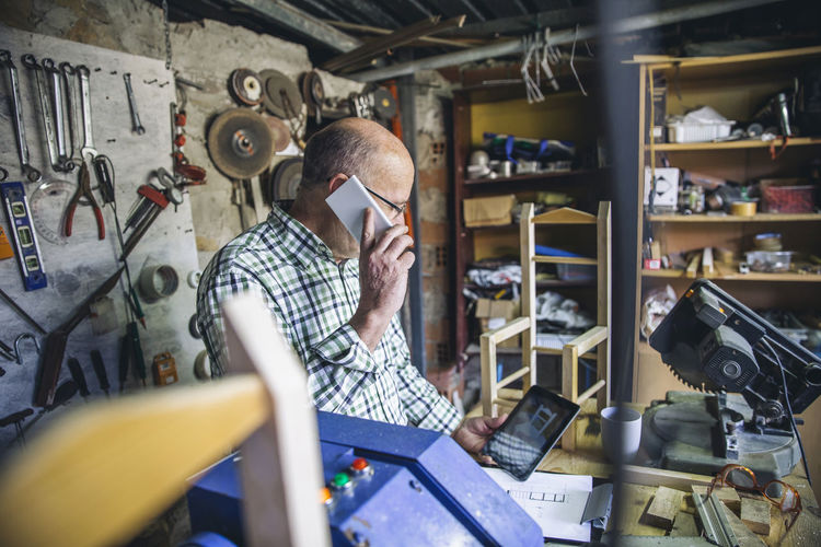 Senior man talking on phone while standing at workshop