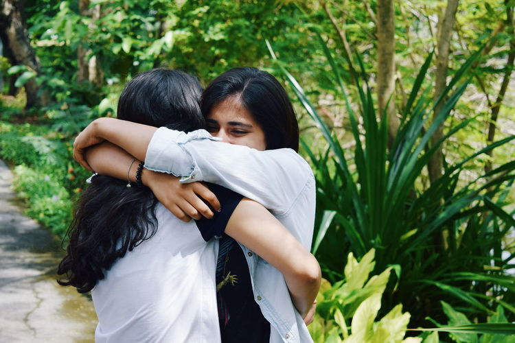 Friends embracing while standing against plants in park