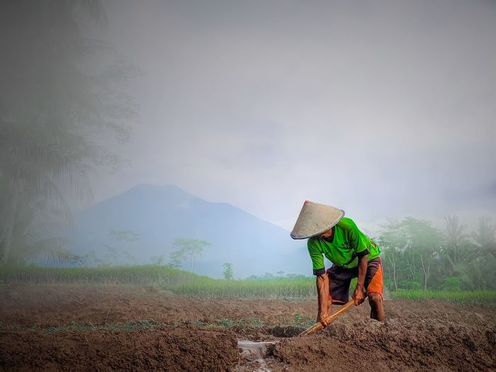 Man working on agricultural field against sky