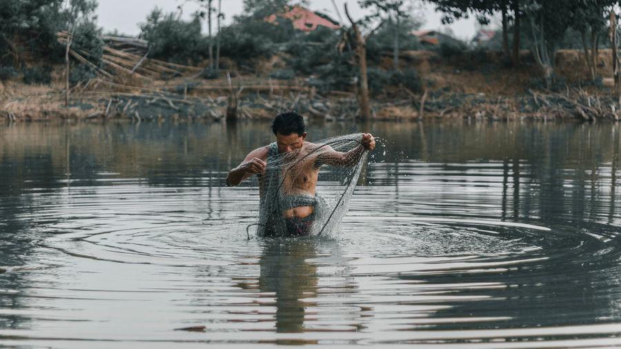 Full length of shirtless man on boat in lake