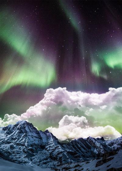 Aurora borealis over snowcapped mountains against sky