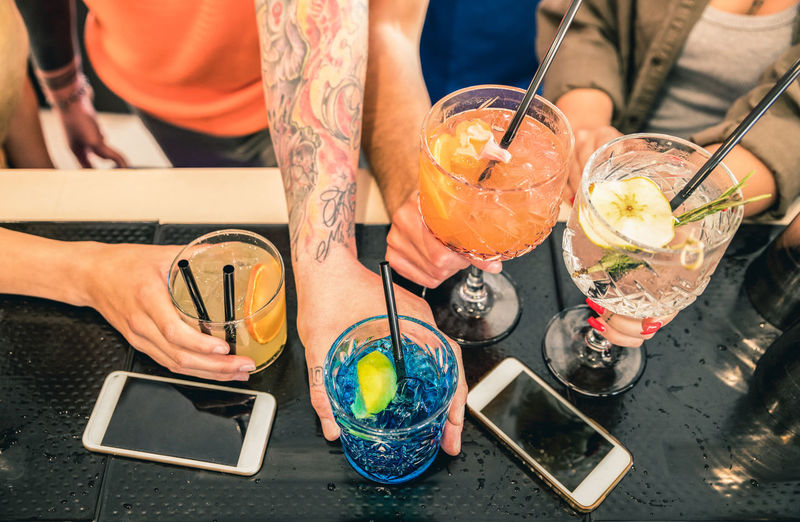 Cropped Hands Of Friends Holding Drinks On Counter In Bar