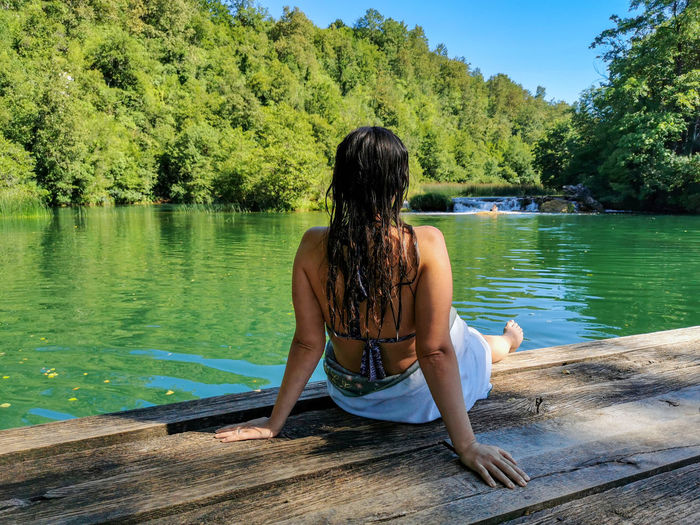Rear view of woman sitting by lake against trees