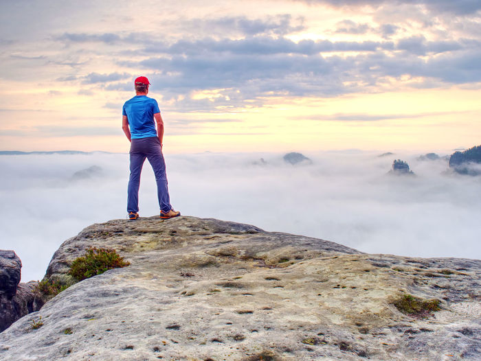 Tall guy with hands in pocket in blue shirt standing and watch the horizon. successful traveler man