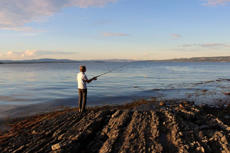 Rear view of man fishing while standing on shore at beach against sky