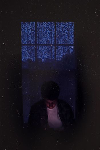 Double exposure of man in darkroom and stars in sky at night