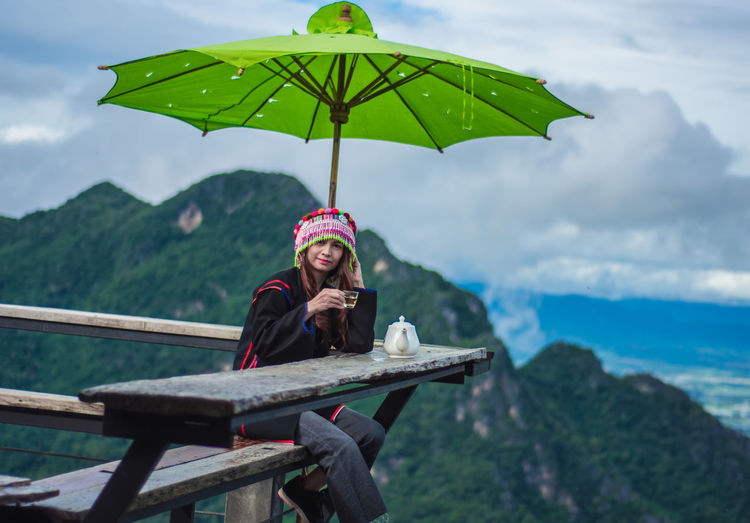 Smiling woman sitting on mountain against sky