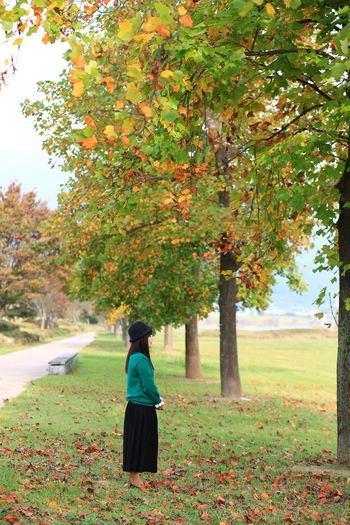 Rear view of woman with autumn leaves