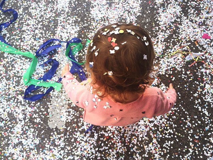 High Angle View Of Child Standing On Street Covered With Confetti