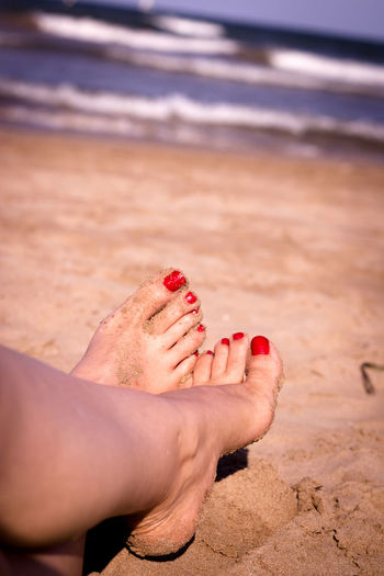 Low section of woman relaxing on sand at sandy beach