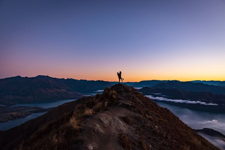 Silhouette couple standing on rock against sky during sunset