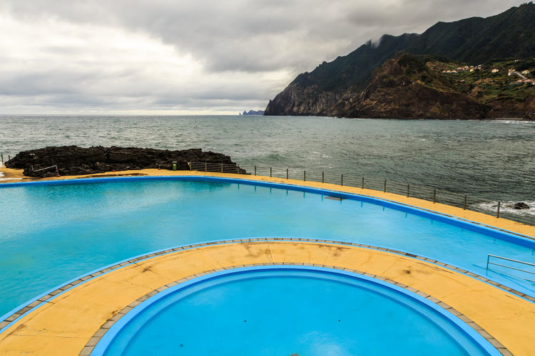 View of swimming pool by sea against sky