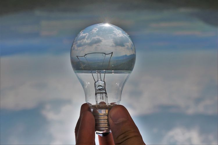 Close-up of hand holding light bulb against sky
