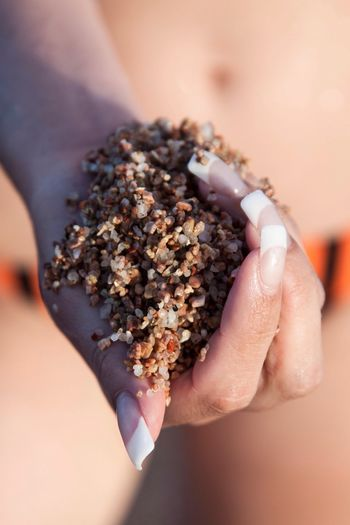 Close-up of hand holding wet sand over blurred background
