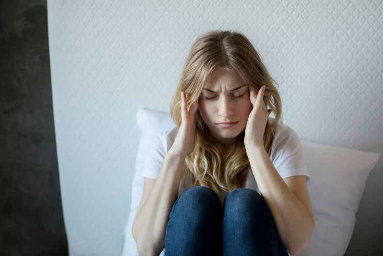 Young woman suffering from headache sitting on bed at home