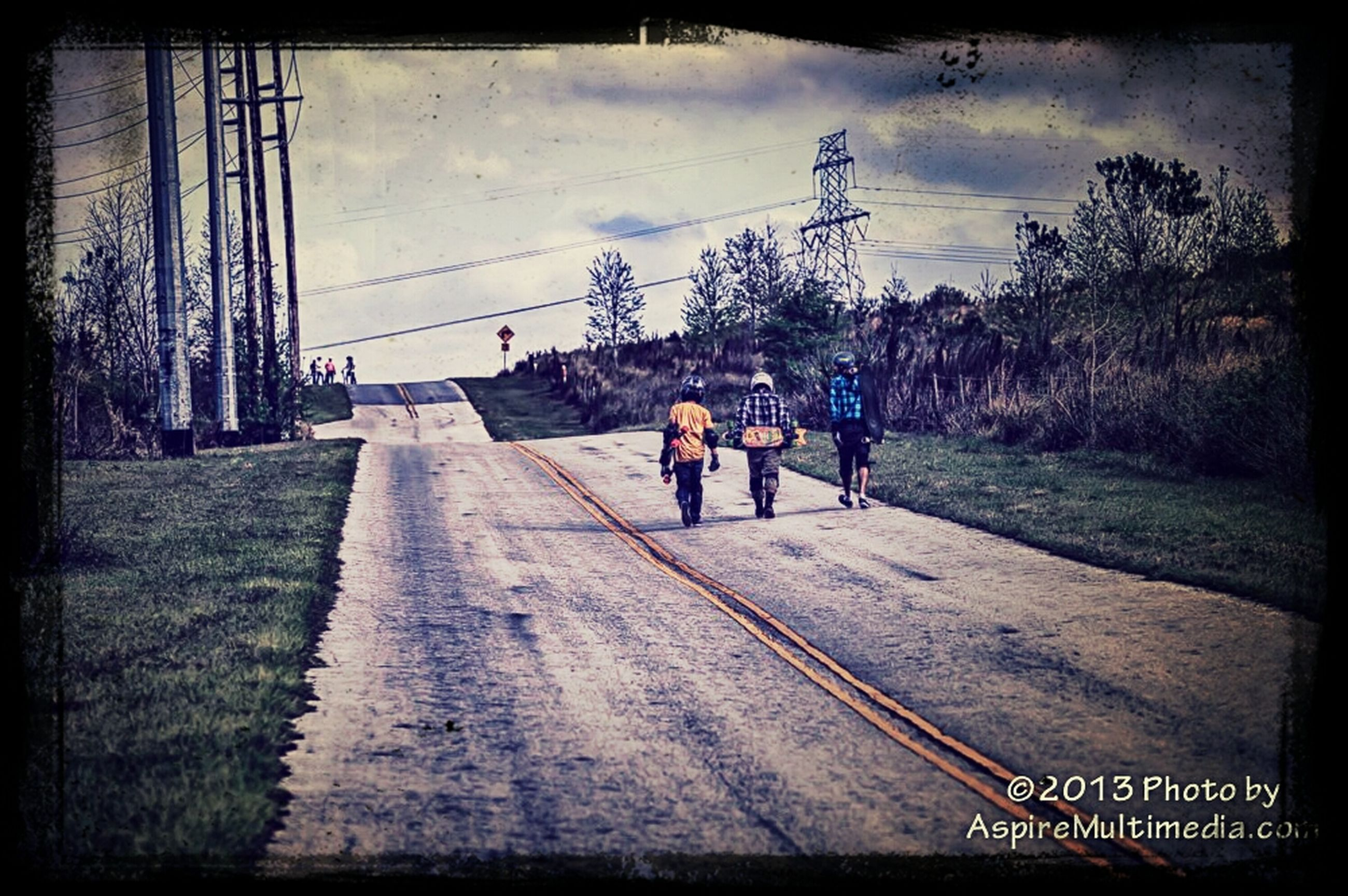 transfer print, auto post production filter, men, lifestyles, walking, full length, sky, leisure activity, person, transportation, rear view, togetherness, the way forward, bicycle, tree, road, cloud - sky