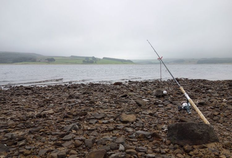 Fishing rod on field by river against sky