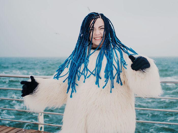 Portrait of woman tossing dyed dreadlocks on boat in sea