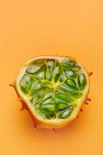 Directly above shot of lemon slice against orange background