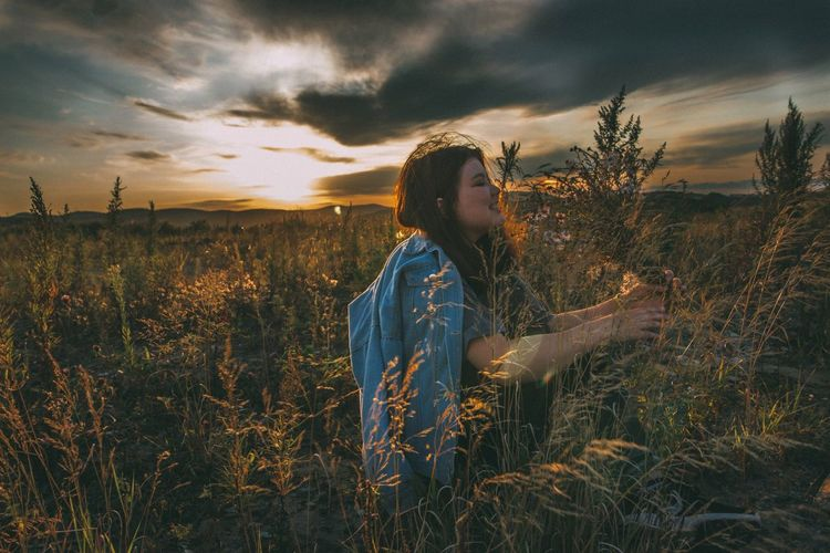 Happy woman standing in field against cloudy sky during sunset