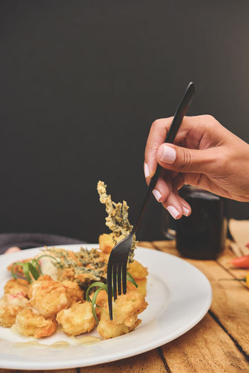 Cropped image of person holding food on table