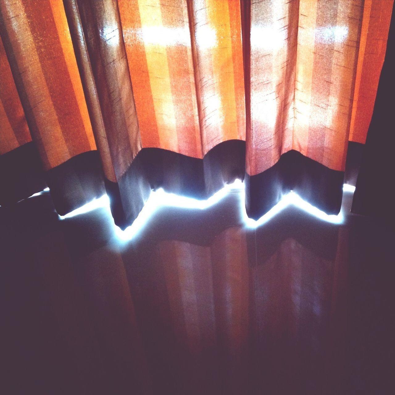 High angle view of illuminated light beam behind curtain
