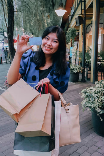 Beautiful fashionable asian woman a is shopping for a lot of goods at a mall using her credit card
