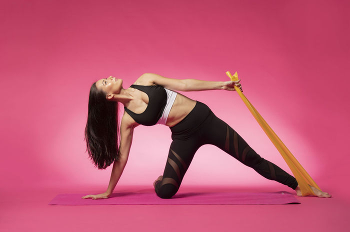 Long haired beautiful pilates or yoga athlete does a graceful pose while wearing a tight sports outfit against a pink background in a studio Body & Fitness Dance Exercising Silhouettes Stretching Legs Workout Flow Yoga Pose Abdominal Muscles Art Background Exercise Ball Fitness Outfit Long Hair Pilates Pilateslovers Pink Color Pose Pretty Girl Rubber Band Sports Clothing Studio Shot