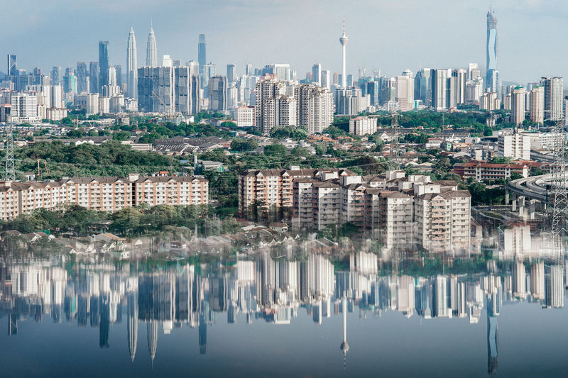 Reflection of buildings in city against sky
