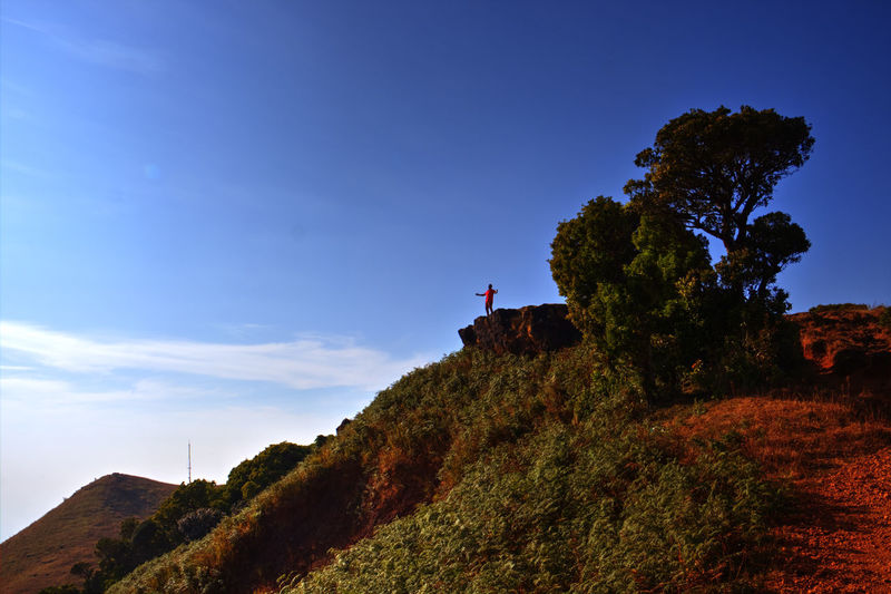 Mid distance view of man standing on cliff against blue sky