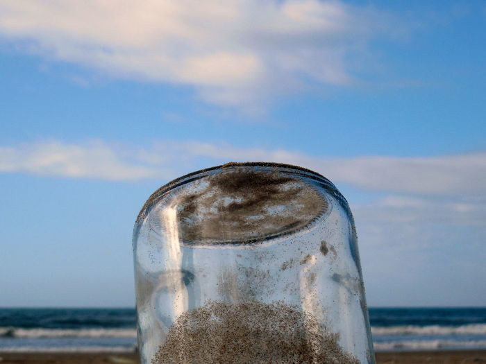 Close-up of glass on beach against sky