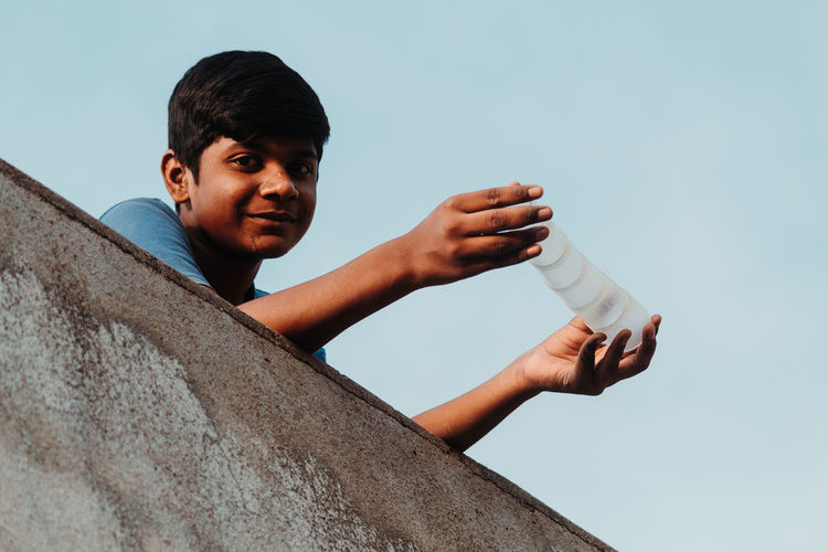 Low angle portrait of boy holding bottle on terrace against clear sky