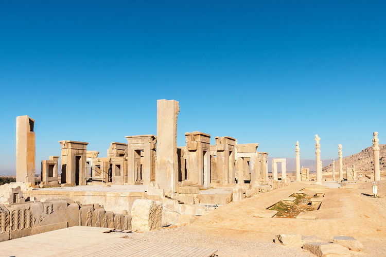 Ruins of ancient temple against clear blue sky
