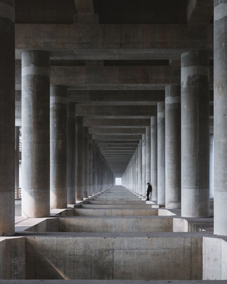 Man standing under bridge