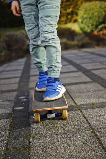 Low section of boy skateboarding on footpath