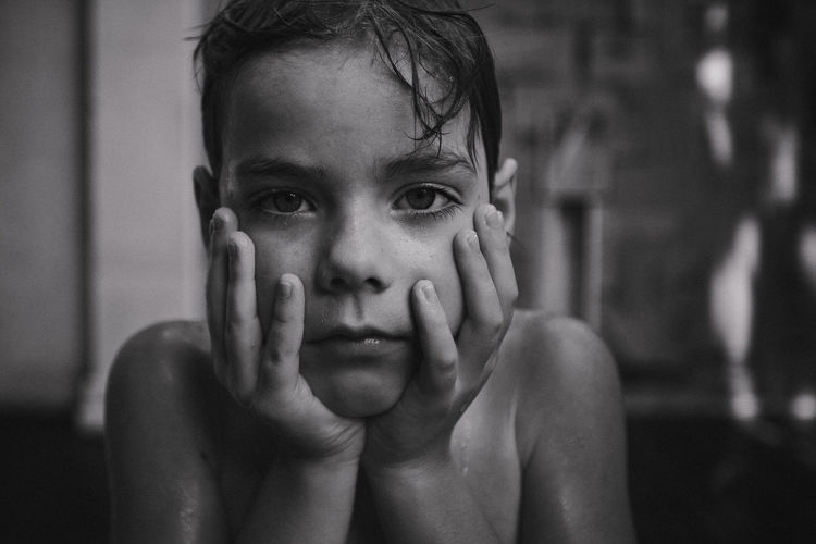 Close-up of shirtless wet boy with head in hands