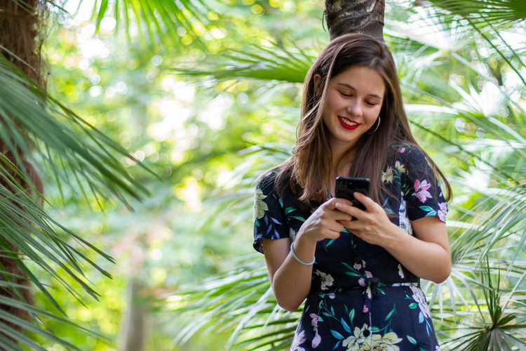 Young woman using mobile phone against trees