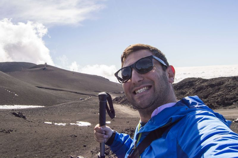 Portrait of happy male hiker standing at mt etna against sky