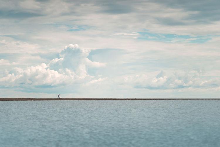 A man runs along the sea spit