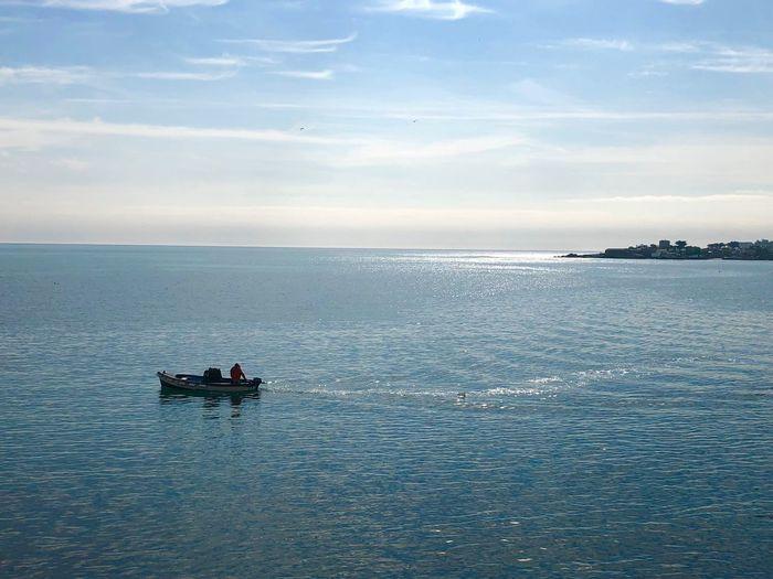 Motorboat in sea against sky