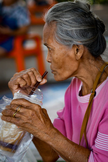 Side view of senior woman having drink