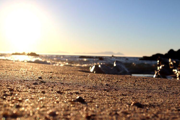 Surface level of beach against clear sky