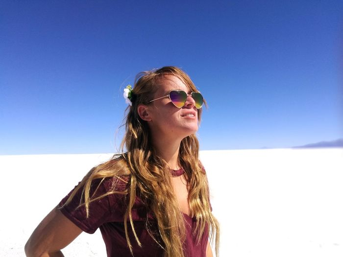 Beautiful young woman standing salar de uyuni against clear blue sky